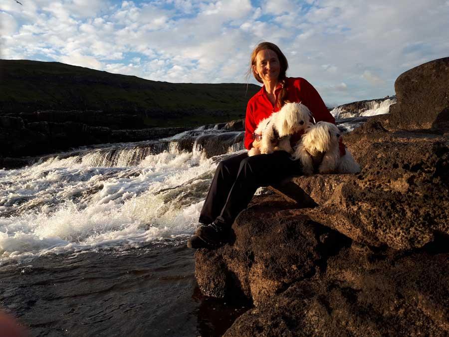 Woman and dog at Bøssdalafossur in Vágar, Faroe Islands